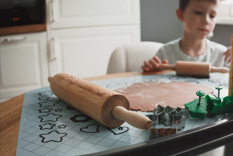 Der Junge kocht Plätzchen in der Hauptküche Nahaufnahme eines Nudelholzes und der Plätzchenschneider Der Junge im Hintergrund ist lizenzfreie stockbilder