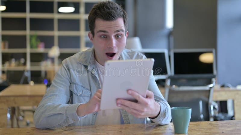 Der junge männliche Designer feiert Erfolg auf dem Tablet im Büro stockfoto