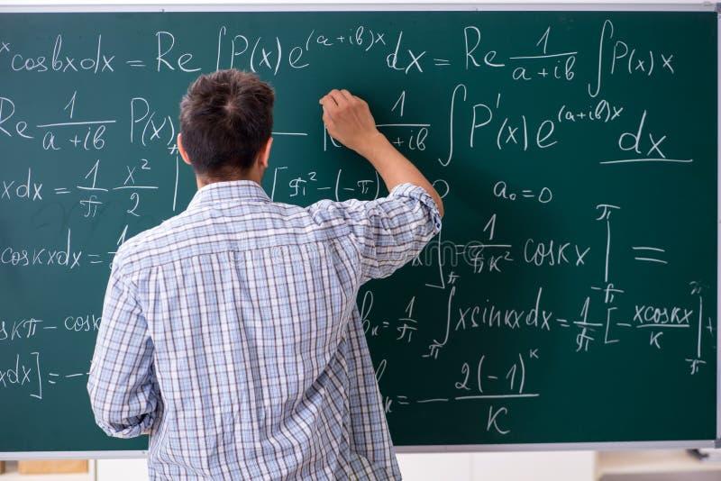 Der junge männliche Student, der in der Schule Mathe studiert lizenzfreie stockfotografie