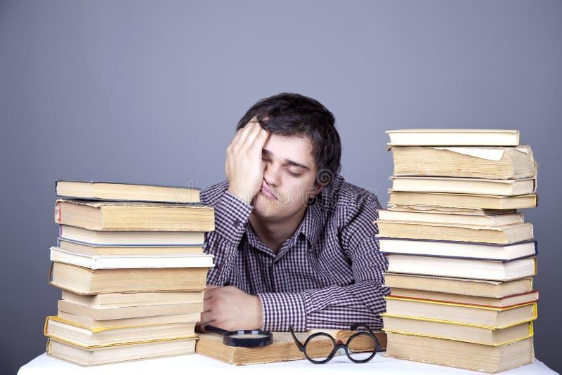 Der junge müde Kursteilnehmer mit den Büchern trennte. stockfotografie