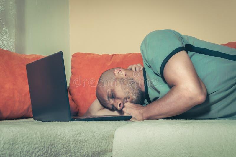 Der junge müde Mann, der eine Pause macht und schlief auf das Bett mit seinem Schossspitzencomputer nach stark und lang on-line-A stockfotografie