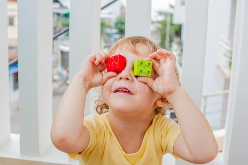 Der Junge macht Augen von bunten Kind-` s Blöcken Netter Kleinkindjunge mit den Gläsern, die mit vielen bunten Plastikblöcken her stockfotografie