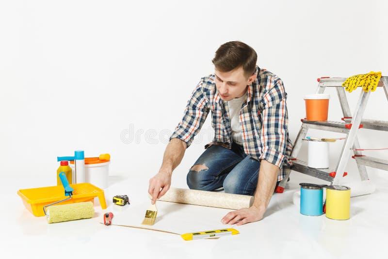 Der junge Mann, der auf Boden mit Tapetenrolle sitzt, bürsten für das Kleben, Instrumente für den Erneuerungswohnungsraum, der an stockfotos