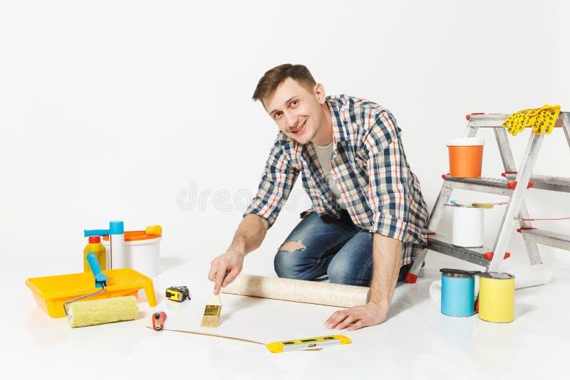 Der junge Mann, der auf Boden mit Tapetenrolle sitzt, bürsten für das Kleben, Instrumente für den Erneuerungswohnungsraum, der an stockfotografie