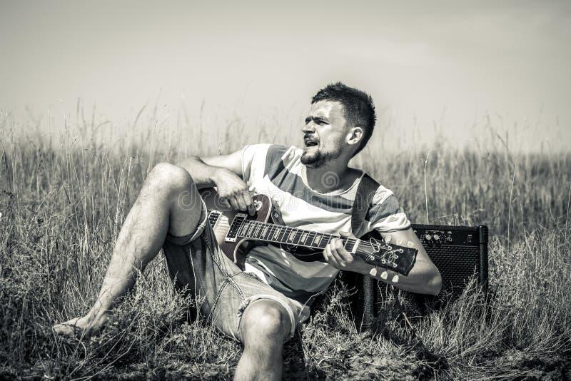 Der junge Mann auf dem Feld, dem Musiker mit der Gitarre und dem Ampere, dem Konzept von Musik und Kunst stockfoto