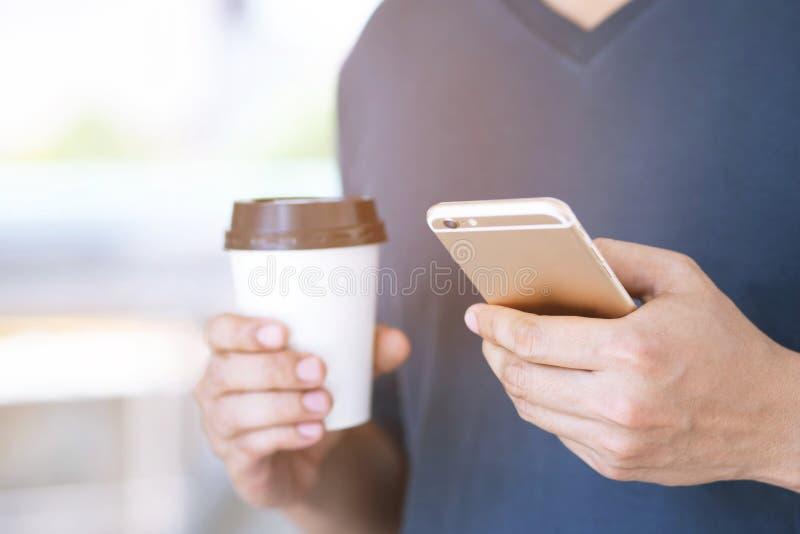 Der junge Mann, der auf Handystand in aufpassender Mitteilung am Handy während der Bruchhand hält Papierschale von verwendet, neh stockfotos