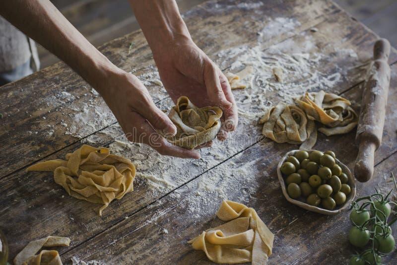 Der junge Mann bereitet selbst gemachte Teigwaren an der rustikalen Küche zu lizenzfreie stockfotografie