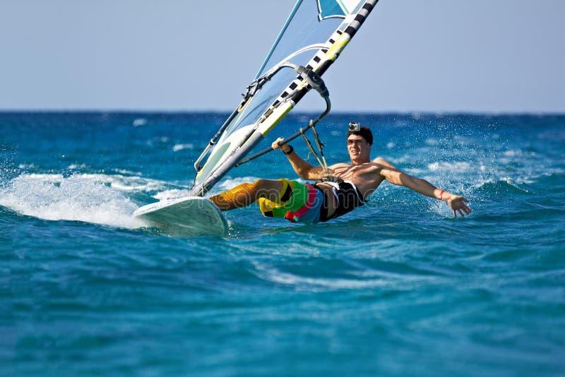 Der junge Mann, der den Wind spritzt surft innen, vom Wasser stockfotos