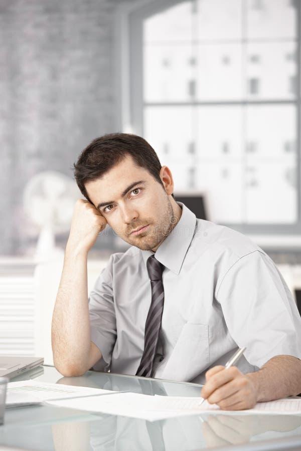 Der junge Mann, der im Büroschreiben arbeitet, merkt das Denken stockfoto