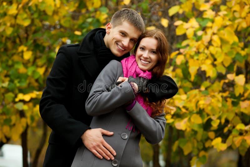Der junge Mann, der seine Frau umarmen und sie lächeln stockfoto