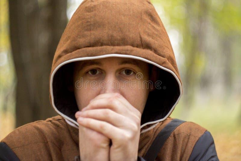 Der junge Mann, der seine Hände wärmt stockfotos
