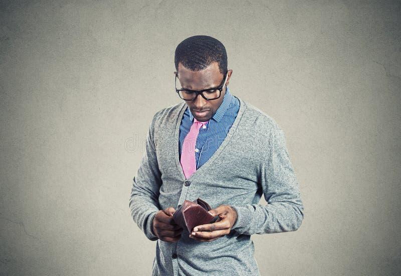 Der junge Mann, der seine leere Geldbörse untersucht, hat kein Geld stockfotografie