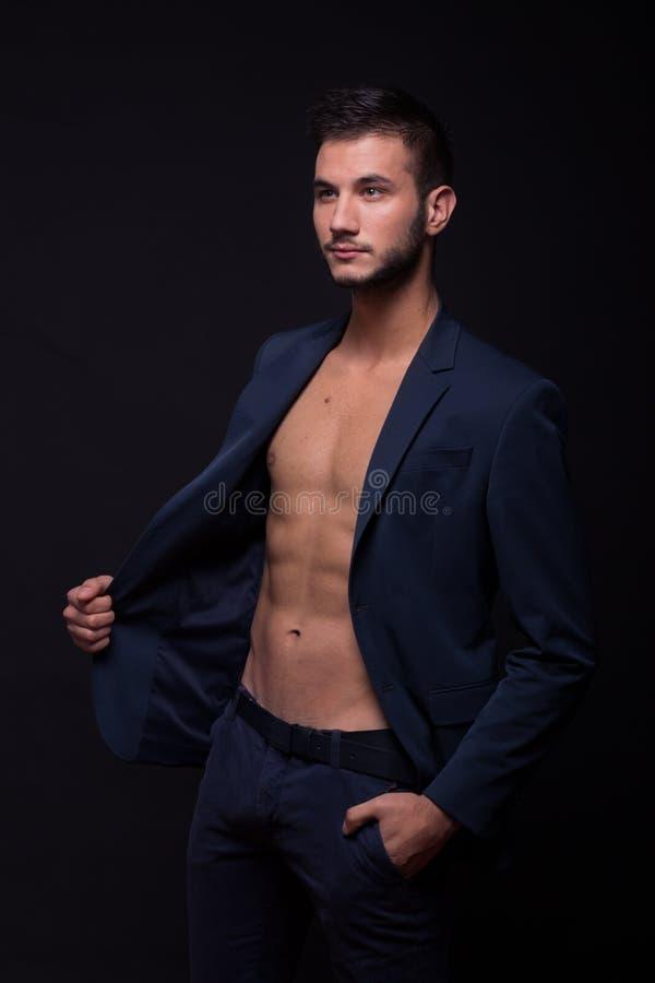 Der junge Mann, der seitlich, hemdlose Anzugsjacke aufwerfend schaut, keucht stockbilder