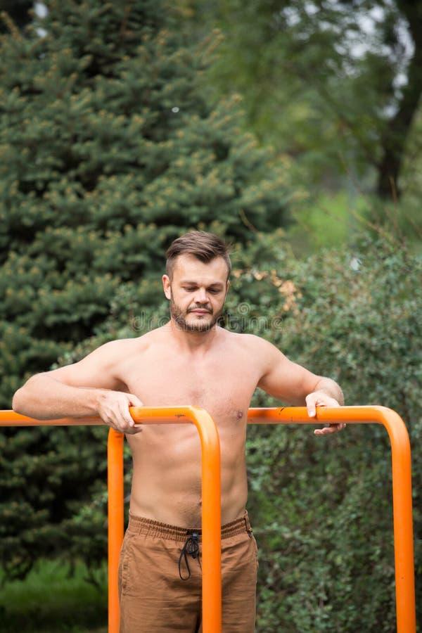 Der junge Mann, der Trizeps tut, tauchen auf Barren draußen ein lizenzfreies stockbild