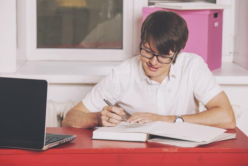 Der junge Mann, der zu Hause am Tisch arbeitet stockfoto
