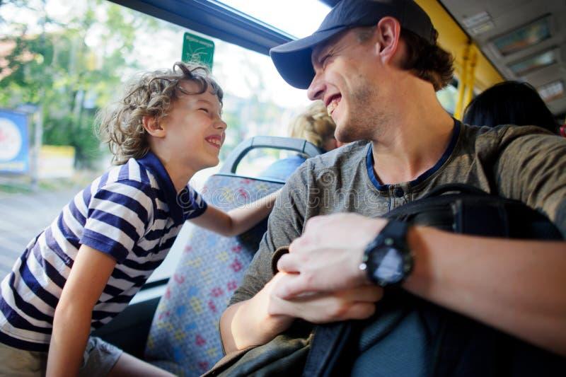 Der junge Mann fährt mit dem Bus zusammen mit dem Sohn stockfoto