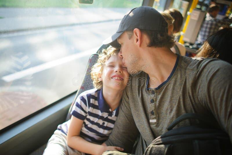 Der junge Mann fährt mit dem Bus zusammen mit dem Sohn lizenzfreie stockfotos
