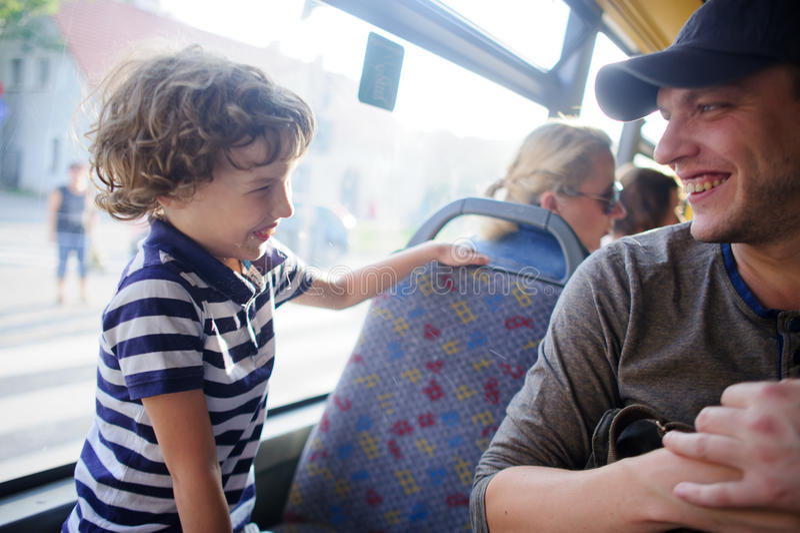 Der junge Mann fährt mit dem Bus zusammen mit dem Sohn lizenzfreies stockbild