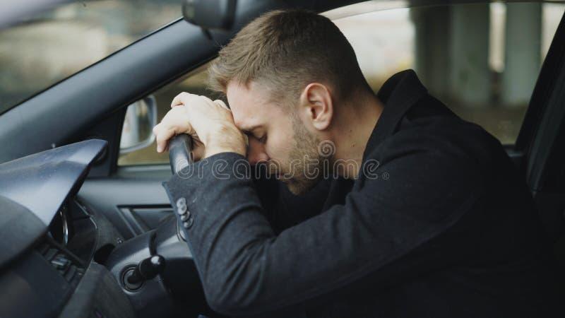 Der junge Mann, der innerhalb des Autos sitzt, ist sehr umgekippt und betont lizenzfreies stockfoto