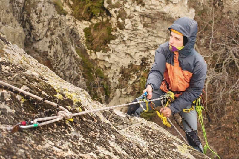 Der junge Mann klettert den Felsen auf einem Seil mit Sicherheitsgurten, Versicherung und Seil, in der vollen Bergsteigerausrüstu stockfotografie
