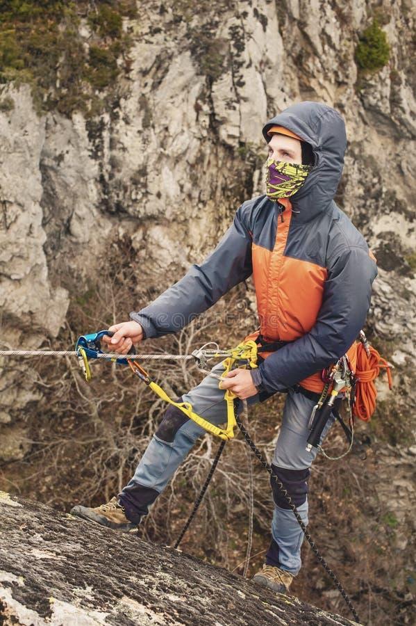 Der junge Mann klettert den Felsen auf einem Seil mit Sicherheitsgurten, Versicherung und Seil, in der vollen Bergsteigerausrüstu lizenzfreie stockbilder