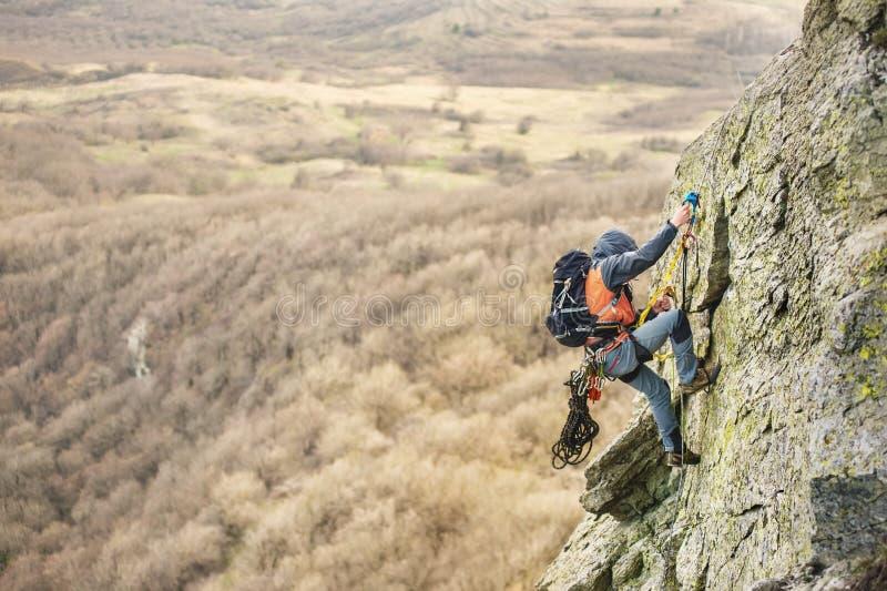 Der junge Mann klettert den Felsen auf einem Seil mit Sicherheitsgurten, Versicherung und Seil, in der vollen Bergsteigerausrüstu stockbild