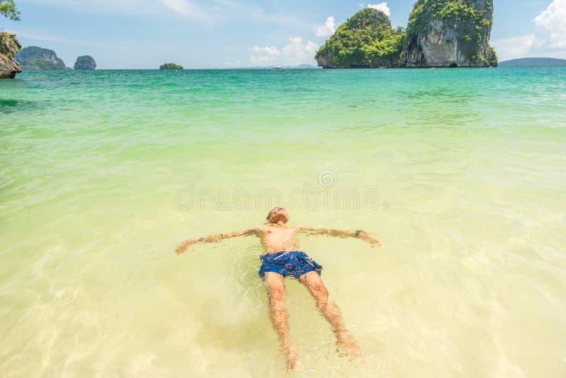 Der junge Mann schwimmt auf dem Rücken in den glasklaren, flachen Meeresgewässern von Phra Nang Phranang Beach, Railay Halbinsel, lizenzfreies stockfoto