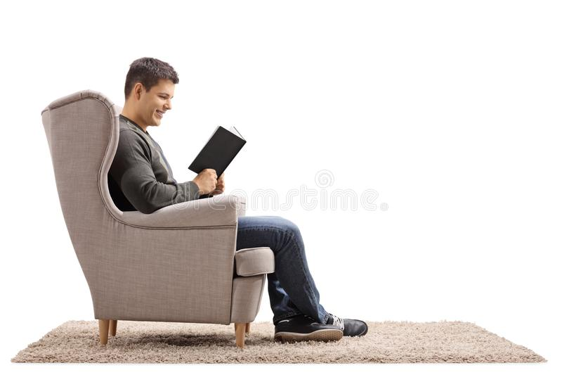 Der junge Mann setzte in einem Lehnsessel ein Buch lesend stockbilder