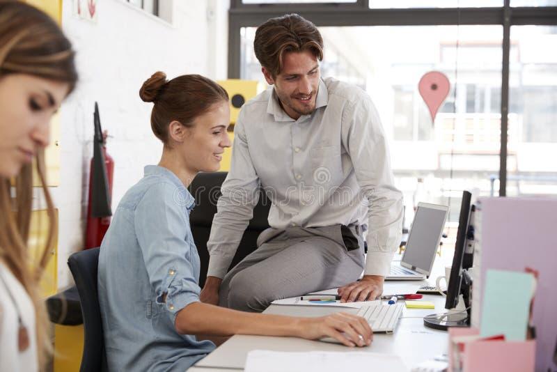 Der junge Mann sitzt auf Frau ` s Schreibtisch im Büro ihre Arbeit besprechend lizenzfreie stockfotografie