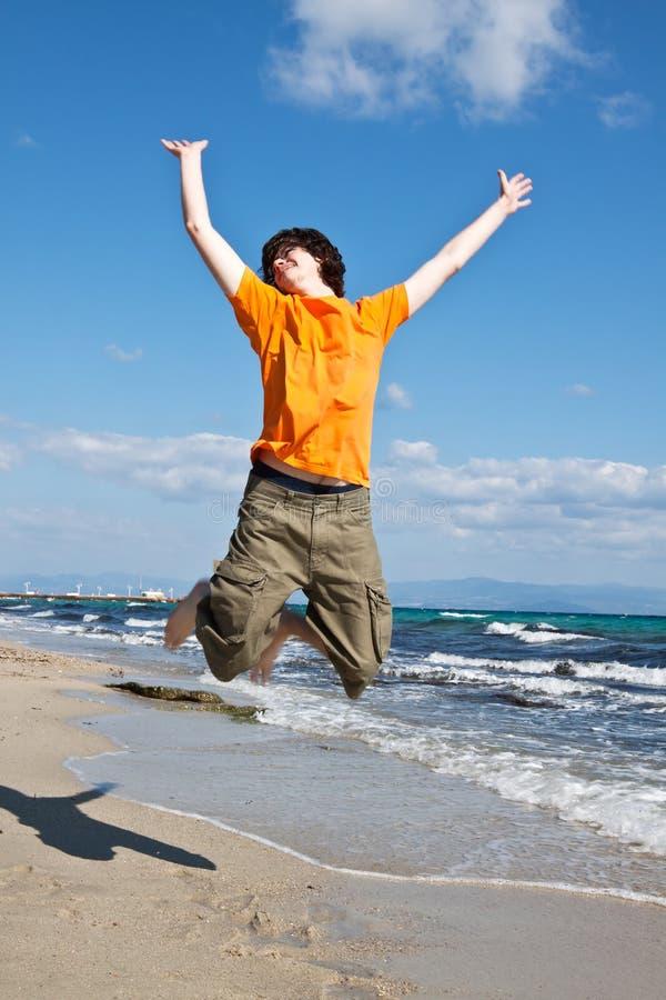 Der junge Mann springt in dem Meer stockfoto