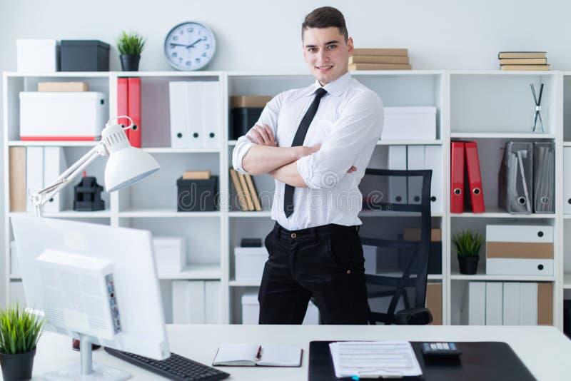Der junge Mann steht im Büro nahe der Tabelle und faltete seine Hände auf seinem Kasten stockbild
