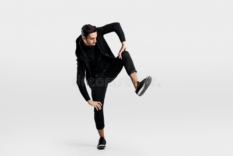 Der junge Mann, der in stilvolle schwarze Kleidung gekleidet wird, hebt ein Bein beim Tanzen des Straßentanzes an lizenzfreie stockfotos