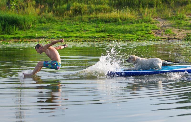 Der junge Mann und der Hund im Boot Die Sprünge von im Wasser stockbild