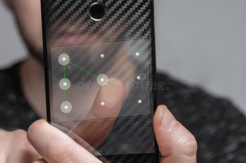 Der junge Mann verwendet die Schablone Identifikation, um das Telefon zu entriegeln lizenzfreie stockbilder