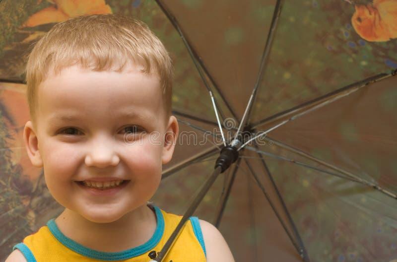 Der Junge mit einem Regenschirm lächelt stockbilder