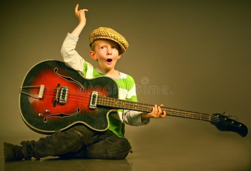 Der Junge mit einer Gitarre lizenzfreies stockfoto
