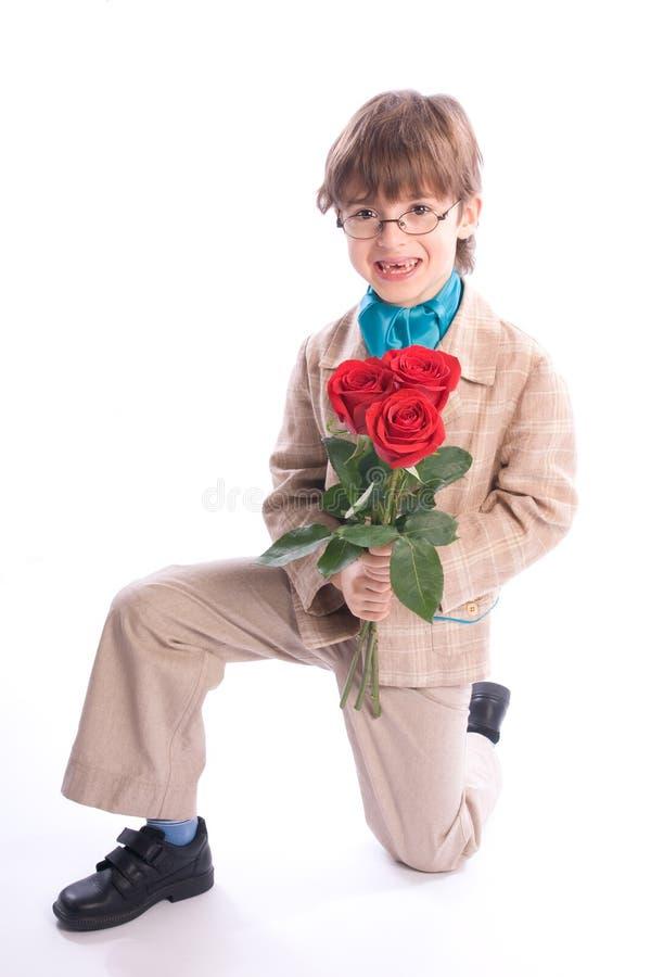 Der Junge mit Rosen auf einem Knie stockfotos