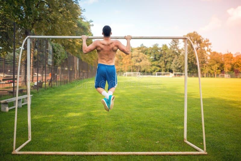 Der junge muskulöse Mann, der Zug tut, ups auf Fußballgericht, eingefleischtes draußen ausbilden stockfotos