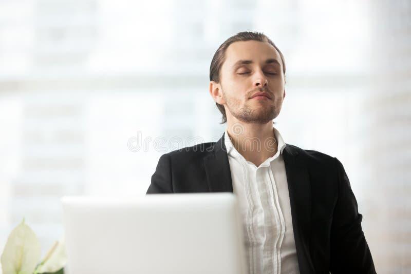 Der junge ruhige Geschäftsmann, der am Arbeitsplatz mit Augen stillsteht, schloss lizenzfreies stockfoto