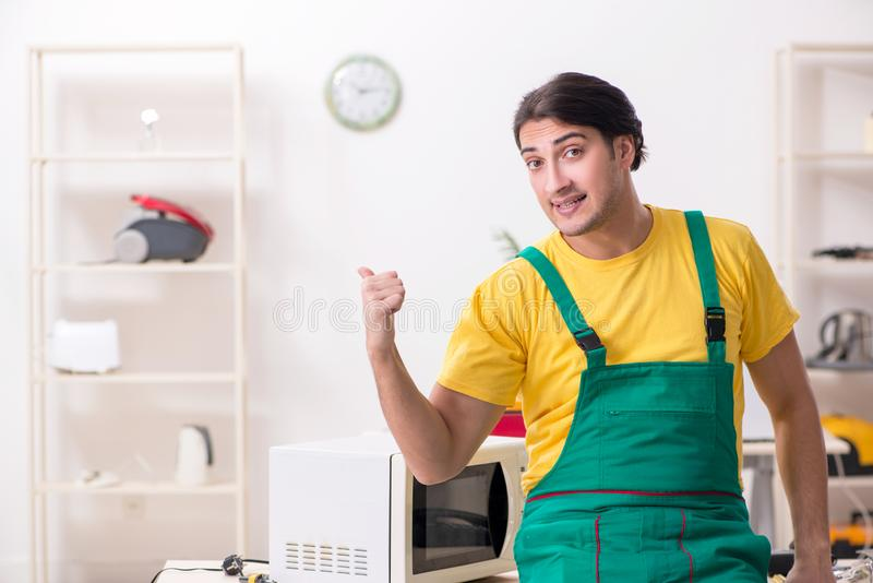 Der junge Schlosser, der im Einsatz Mitte der Mikrowelle repariert stockbild