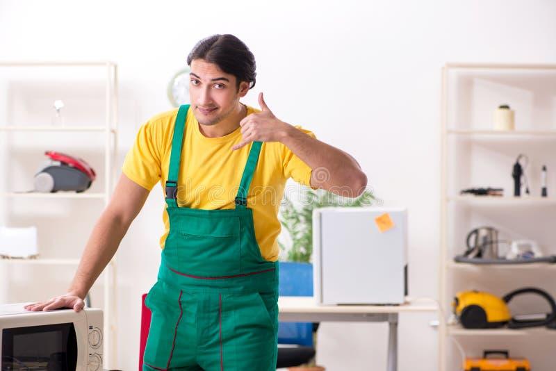 Der junge Schlosser, der im Einsatz Mitte der Mikrowelle repariert lizenzfreies stockfoto