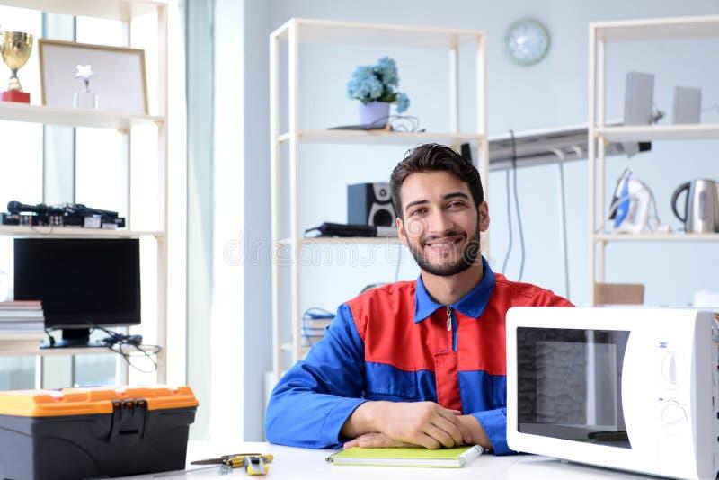 Der junge Schlosserfestlegungs- und -reparaturmikrowellenherd lizenzfreies stockfoto