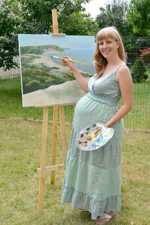 Der junge schwangere weibliche Künstler schreibt ein Bild mit Ölfarbe lizenzfreies stockbild