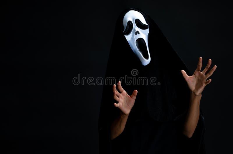 Der Junge in der schwarzen Abdeckung mit der weißen Geistmaske cosplay zu Teufelwechselstrom stockfotografie