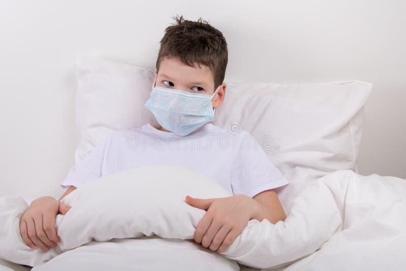 der Junge setzte an eine schützende medizinische Maske, um sich vor Infektion zu schützen stockbild