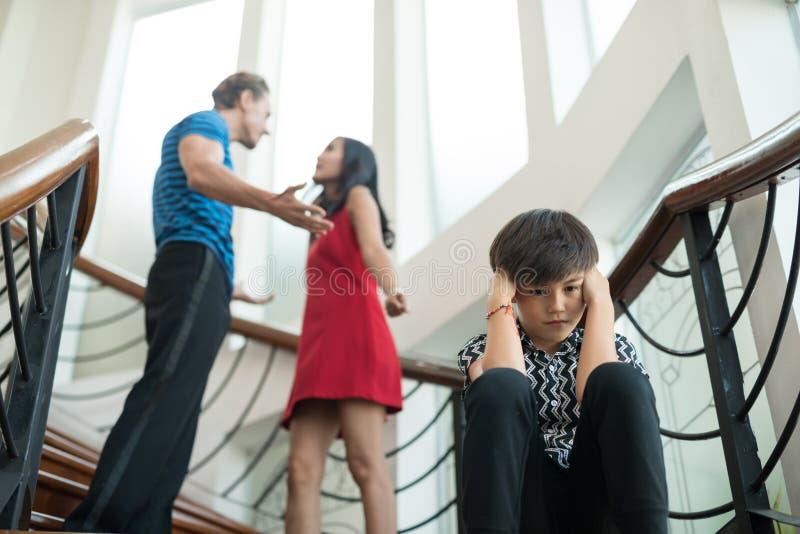 Der Junge sitzen auf der Treppe zu Hause, Eltern streiten Familie probl lizenzfreie stockbilder