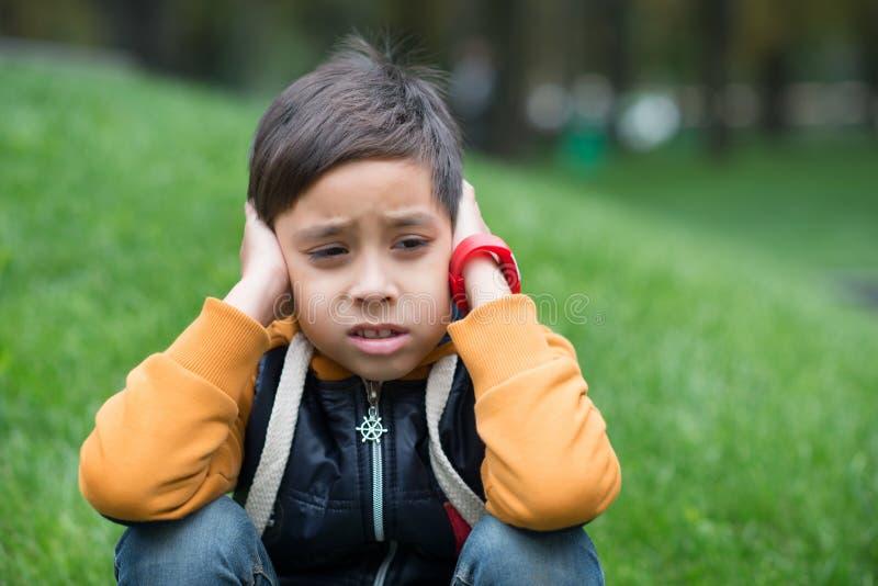Der Junge sitzt auf einem Rasen und denkt lizenzfreie stockfotografie