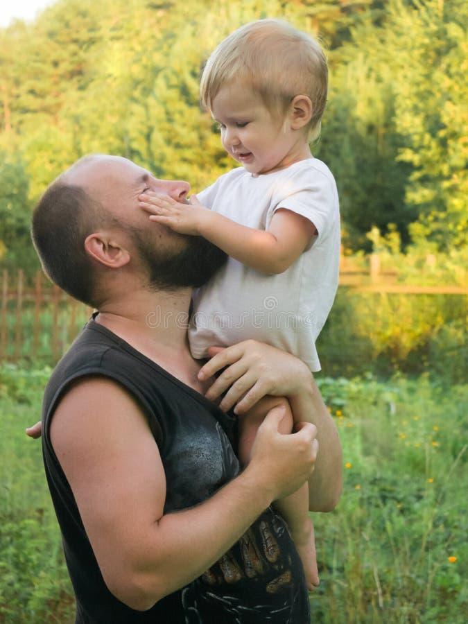 Der Junge sitzt auf seiner Vater ` s Schulter lizenzfreie stockfotografie