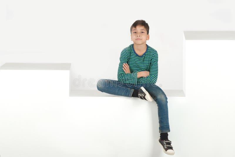 Der Junge sitzt auf weißen Schritten oder Kästen stockbild