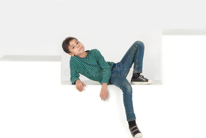 Der Junge sitzt auf weißen Schritten oder Kästen lizenzfreies stockbild